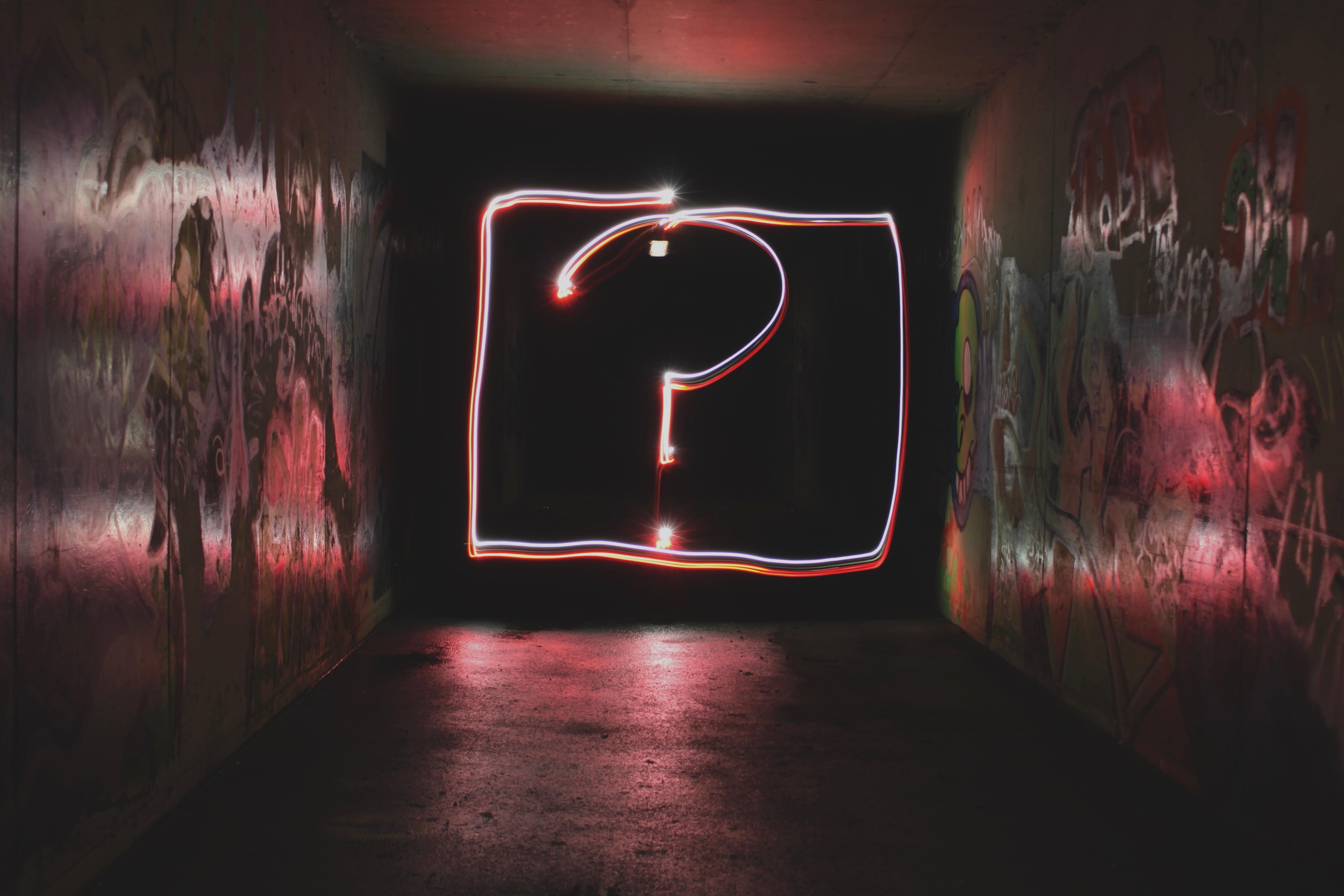 A bright question mark in a dark room